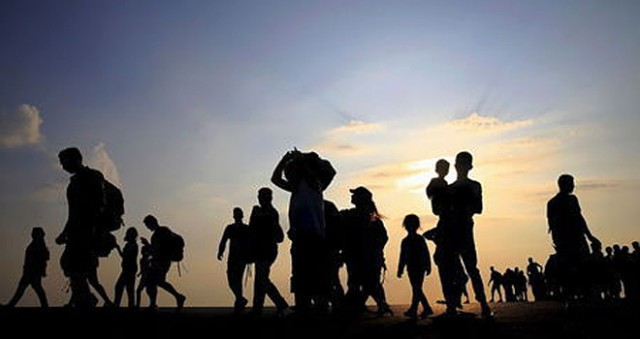 Syrian refugees from Kobani walk at the port of Kos following a rescue opperation off the Greek island of Kos August 10, 2015.  REUTERS/Yannis Behrakis